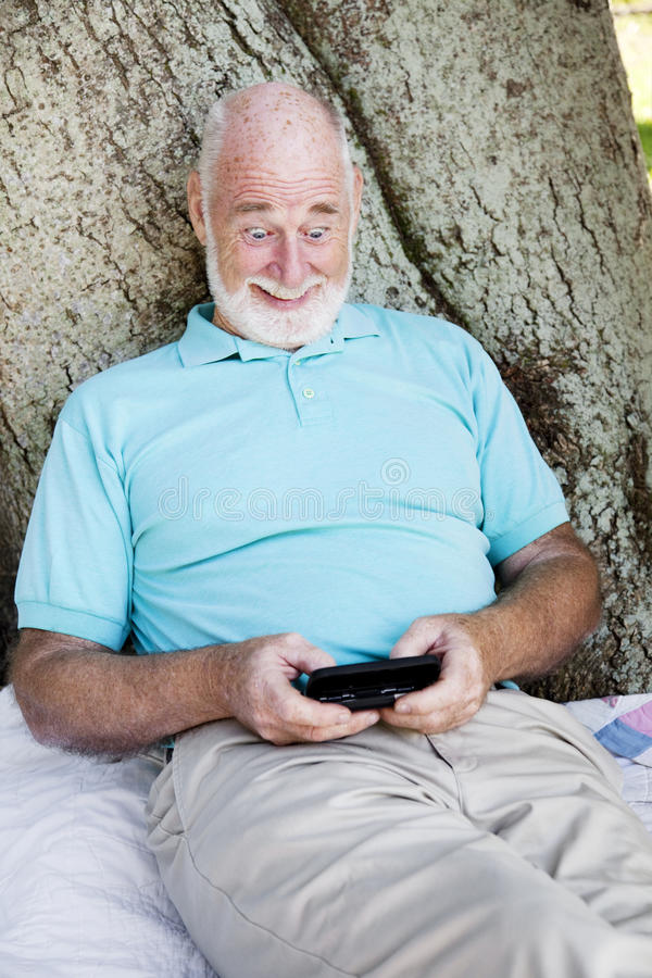 Racy Text Message. Shocked senior man gets a racy, text message from his wife royalty free stock image