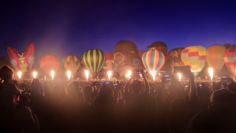 Rad av ballonger för varm luft som tänds upp på natten fotografering för bildbyråer