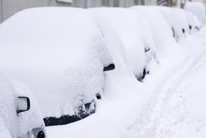 Rad av bilar som täckas i insnöat en parkeringsplats arkivfoton