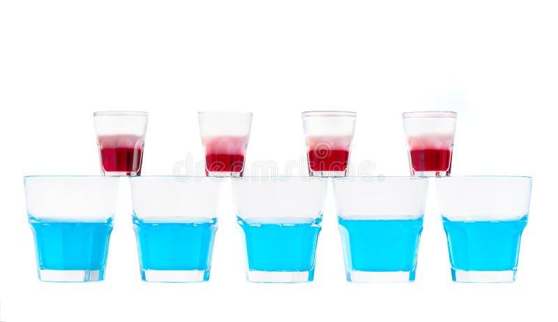 Rad av blåa nya alkoholcoctailar i ett exponeringsglas och rad av glasse arkivbilder