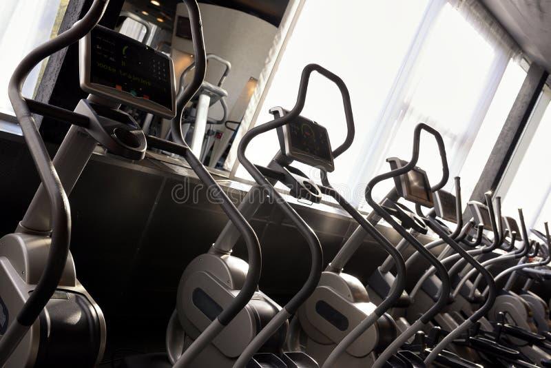 Rad av den ellipsformiga arga instruktören i modern fitnessportklubba royaltyfria foton