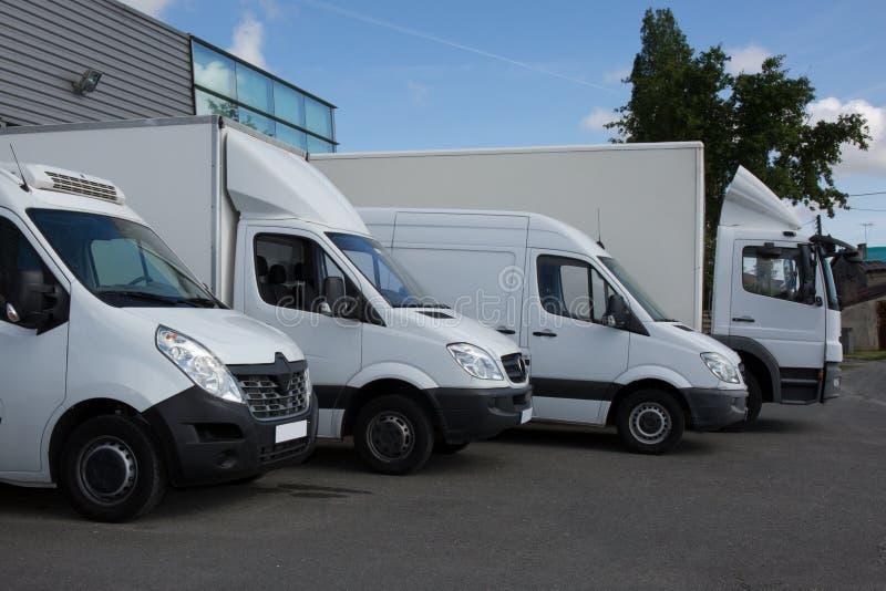 Rad av den vita leverans- och serviceskåpbilen, lastbilar och bilar framme av en fabrik och ett lager arkivfoto