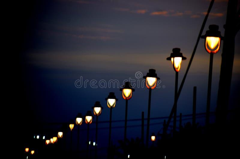 Rad av dunkla ljus nära en strand i natt royaltyfria bilder