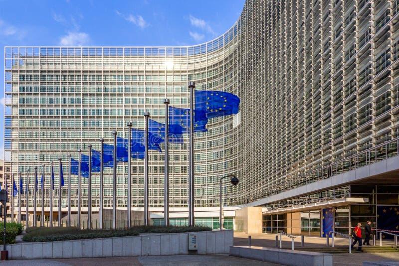 Rad av EU-flaggor framme av kommissionbyggnaden för europeisk union i Bryssel arkivbilder