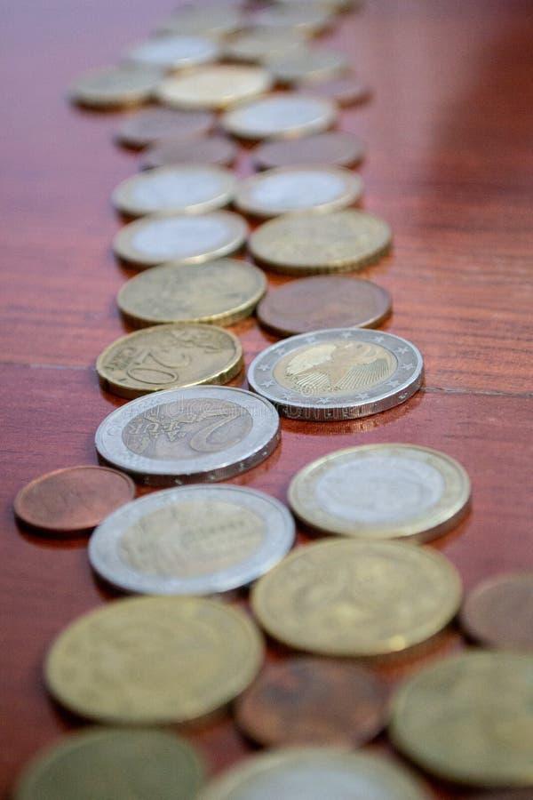 Rad av euromynt p? ett tr? royaltyfri bild