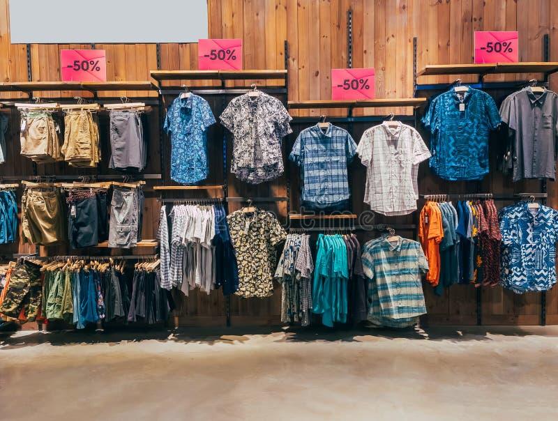 Rad av färgrik mandräkt på skuldrahängare av på boutique i galleria Kläder som hänger på kuggen Uppsättning av den tillfälliga ma arkivbilder