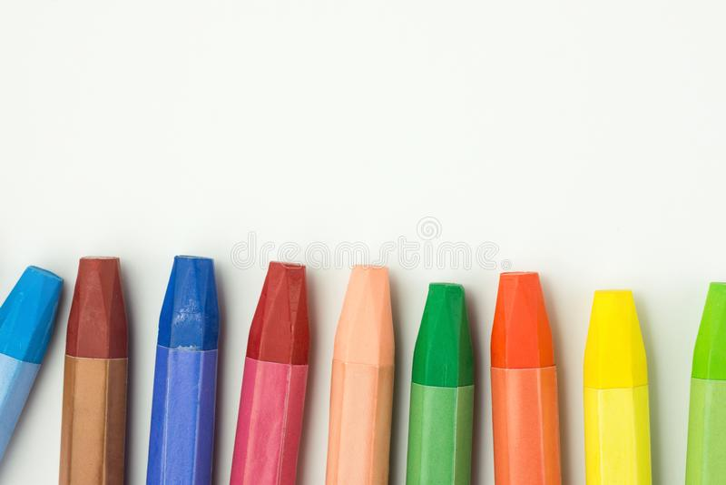 Rad av färgrika mångfärgade pastellfärgade vaxfärgpennor på vitbok Dra tillbaka till begreppet för hobbyen för teckningen för kre fotografering för bildbyråer