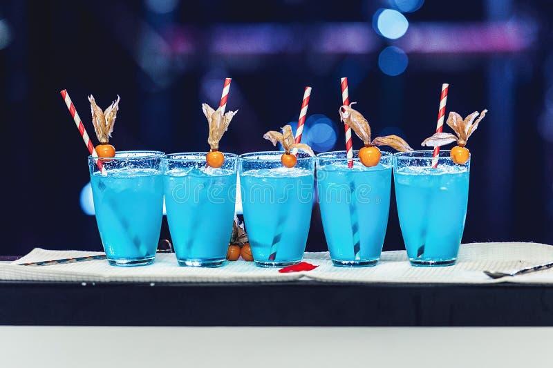 Rad av fem blåa coctailar med is och rör, tillbaka ljus arkivbild