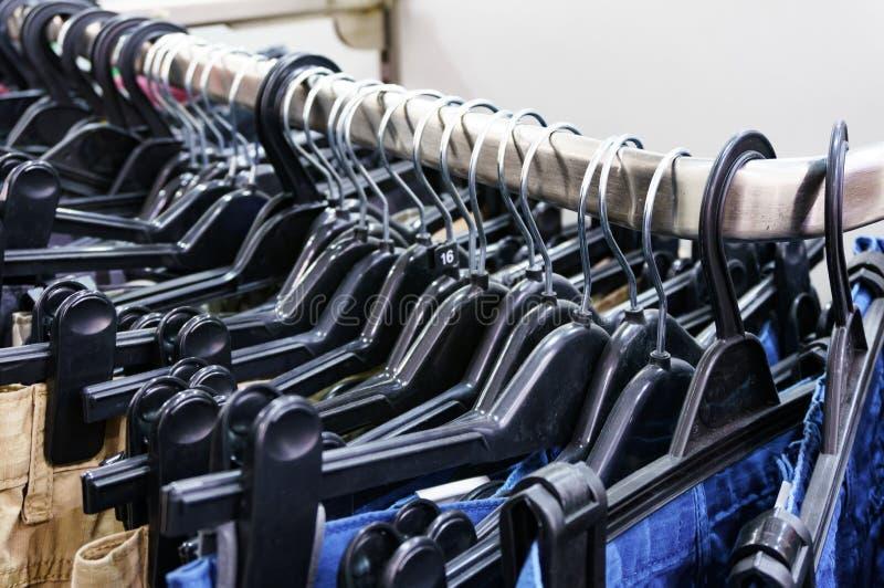 Rad av flåsanden och jeans på hängarna royaltyfri foto