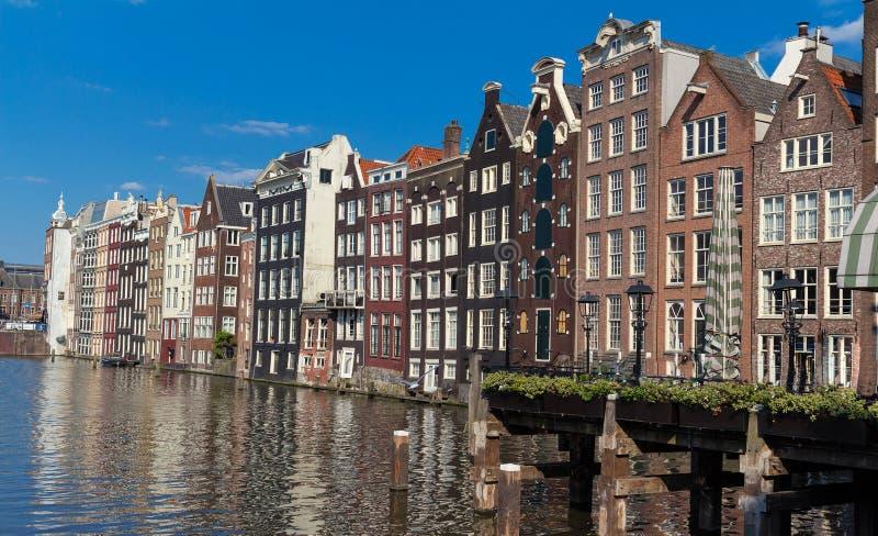 Rad av forntida kanalhus i den holländska huvudstaden Amsterdam mot en blå himmel royaltyfria bilder