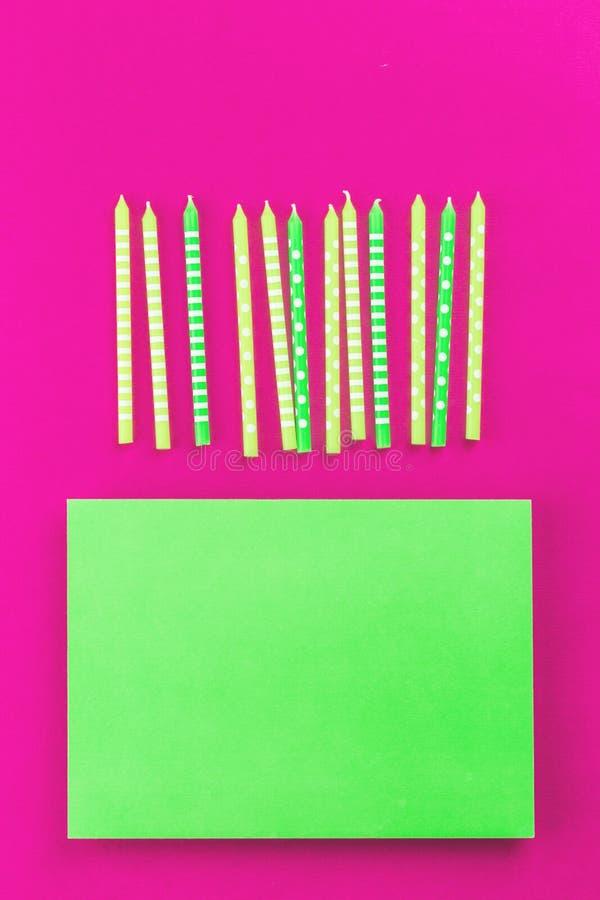 Rad av gröna stearinljus för neon på rosa bakgrund royaltyfri bild