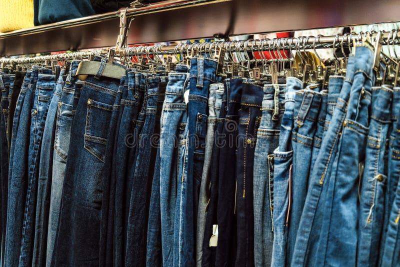 Rad av grov bomullstvillflåsanden som hänger på trempels Jeans i klädlager royaltyfria bilder