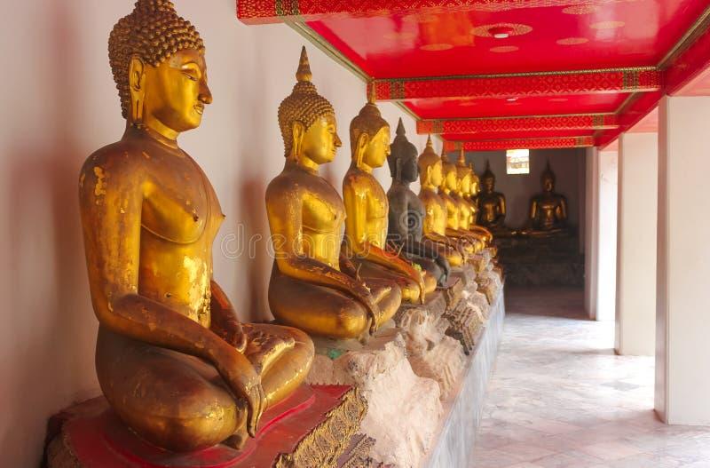 Rad av guld- Buddhastatyer på Wat Phra Kae, tempel av Emerald Buddha, Bangkok, Thailand arkivbilder