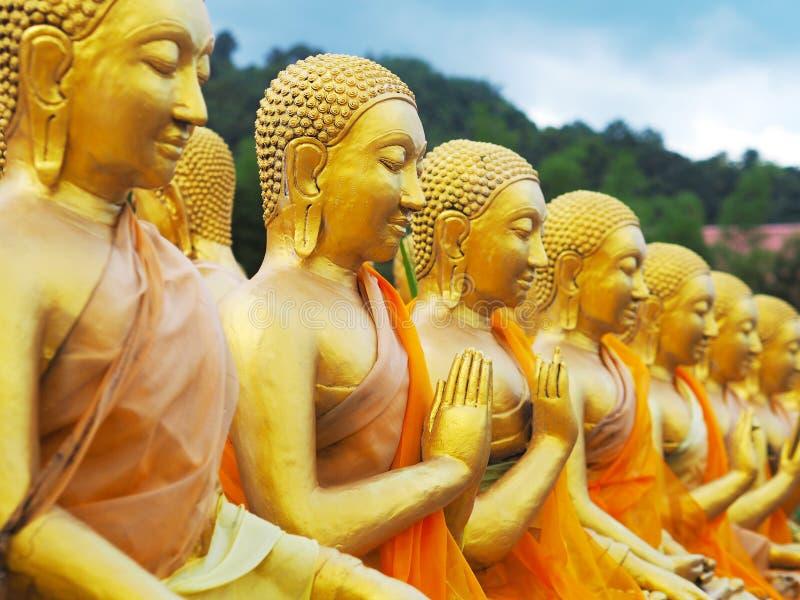 Rad av guld- munkstatyer som sitter i olika gester arkivbild