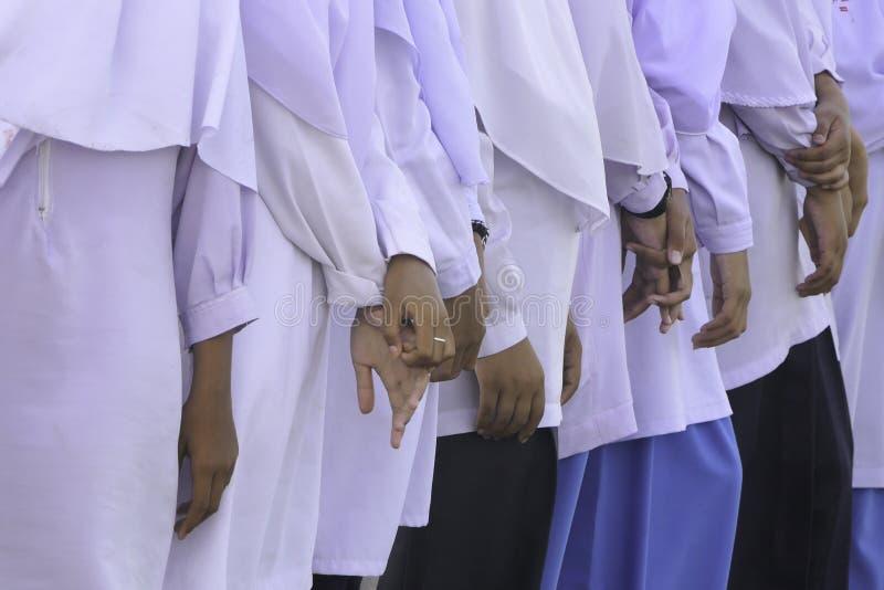 Rad av händer av muslim skolaflickor royaltyfria foton