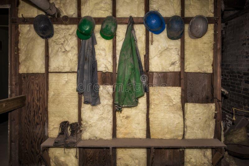 Rad av hårda hattar på den grova väggen arkivfoto