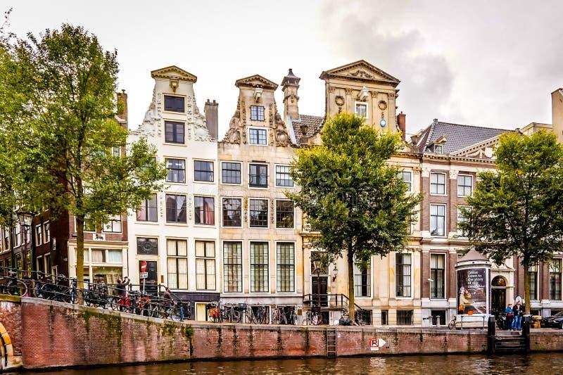 Rad av historiska hus med utsmyckade Klocka och halsgavlar längs de Herengracht gentlemännens kanal i Amsterdam arkivfoto