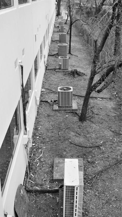 Rad av industriella styrkaluftkonditioneringsapparater bak byggnad royaltyfri foto