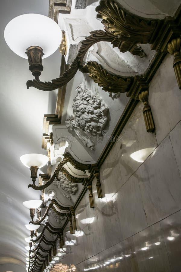 Rad av lyxiga vägglampor och stuckaturprydnader på de vita glansiga marmorväggarna arkivfoton