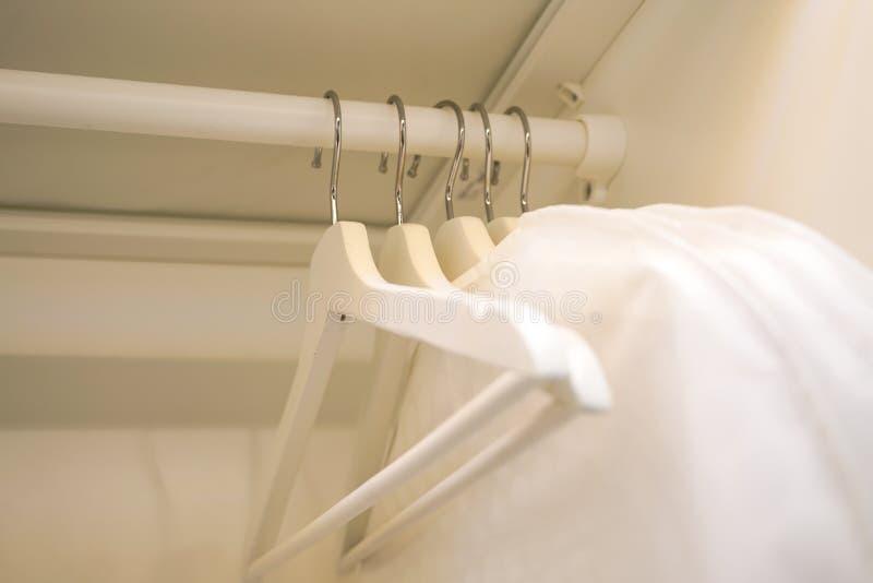 Rad av män och kvinnaskjortor på hängaren som hänger i garderoben arkivfoto