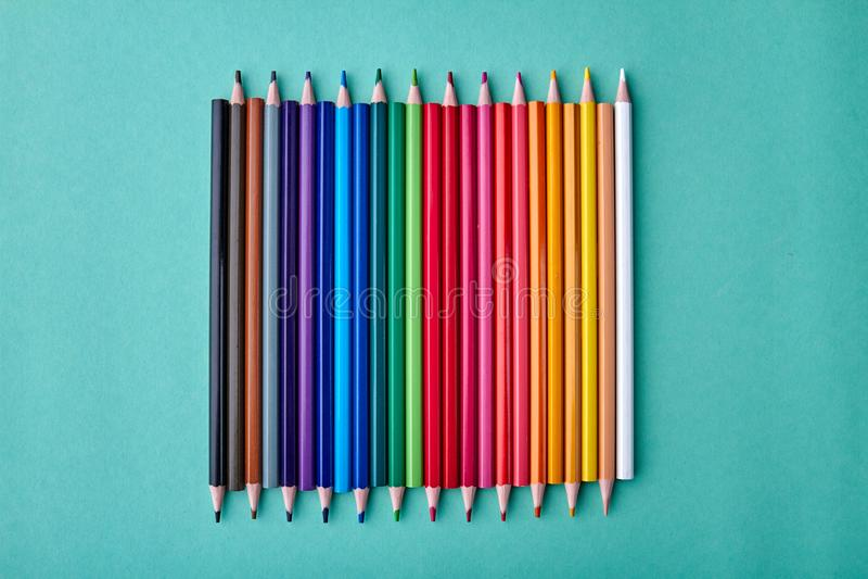 Rad av mångfärgade blyertspennor på färgbakgrund royaltyfri bild