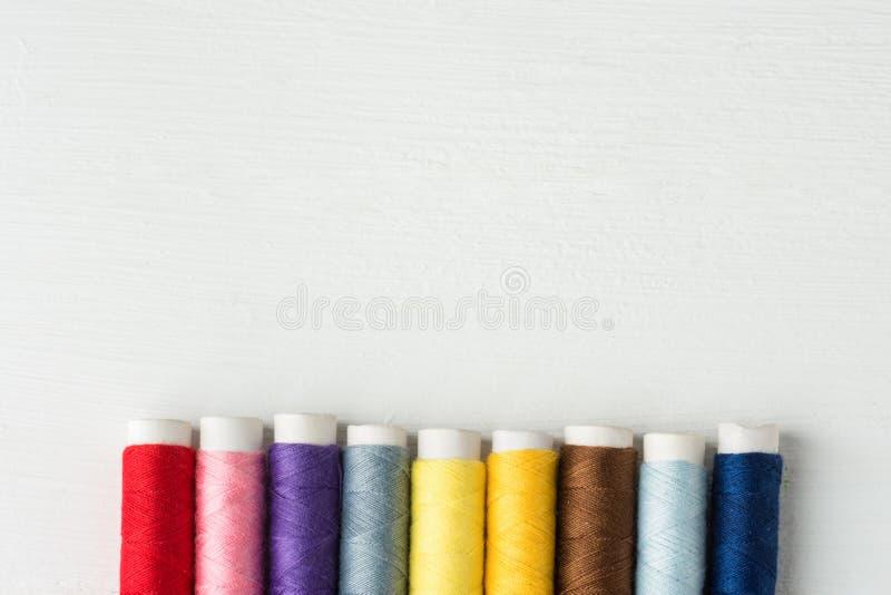 Rad av mångfärgade trådar för regnbågepalettsömnad på papprullar Vit Wood bakgrund Affär för hantverkhobbyhantverkare fotografering för bildbyråer
