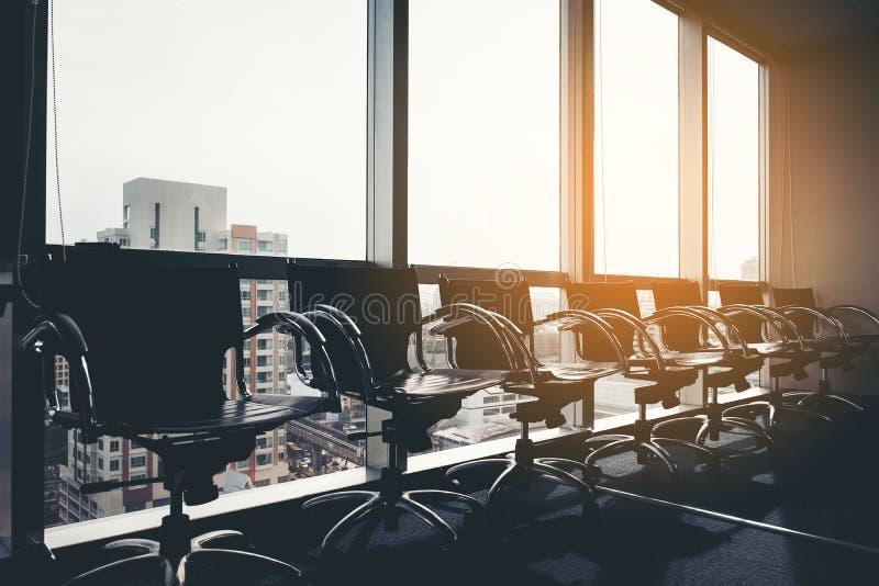 Rad av modern svart stol i tomt kontorsutrymme med stor fönstersiktscityscape, process för tappningbildstil, affärsmöte royaltyfri fotografi