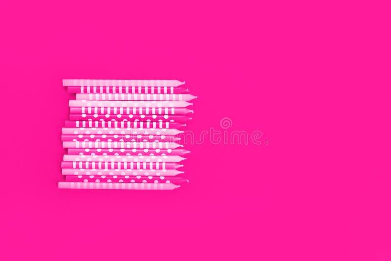 Rad av neonstearinljus på rosa bakgrund arkivfoto