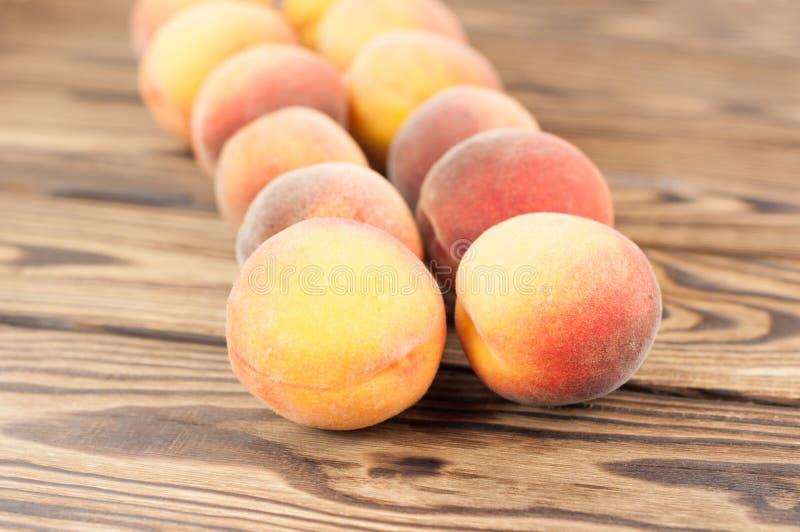 Rad av nya hela mogna persikor royaltyfri foto