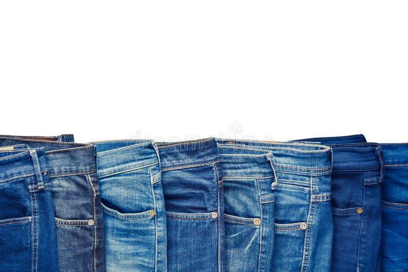 Rad av olik jeans för mode som isoleras på vit arkivbilder
