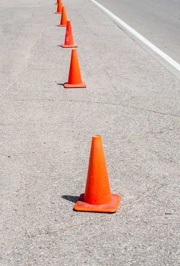 Rad av orange trafikkottar arkivfoton