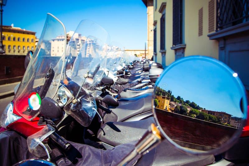 Rad av parkerade motocars, cykel Sikter av Florence - berg, cypressar, hus, reflekterade i spegel för bakre sikt, Florence, Tusca arkivfoton