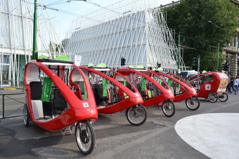Rad av röda schweiziska moderna trishaws som parkeras i den Castello Sforzesco fyrkanten i Milan fotografering för bildbyråer