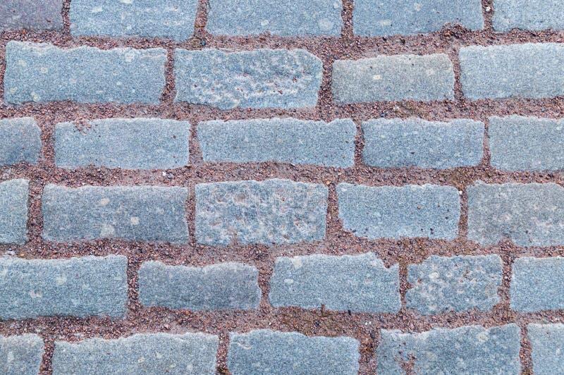 Rad av rektangulära gråa tegelplattor för sten med modellen för sand för terrakottabruntgrus royaltyfria bilder