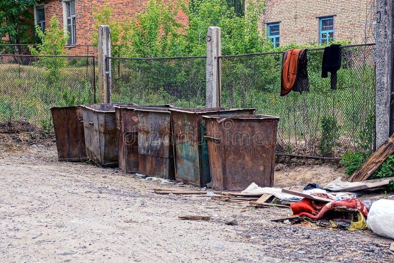 Rad av rostiga smutsiga avskrädebehållare på gatan nära staketet arkivbilder