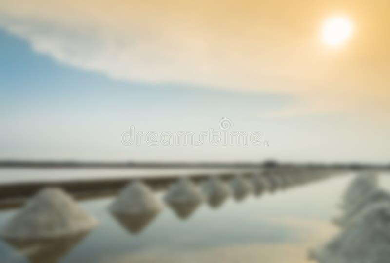 Rad av salt i den salta pannan med blå himmel i suddighetsstil arkivbild