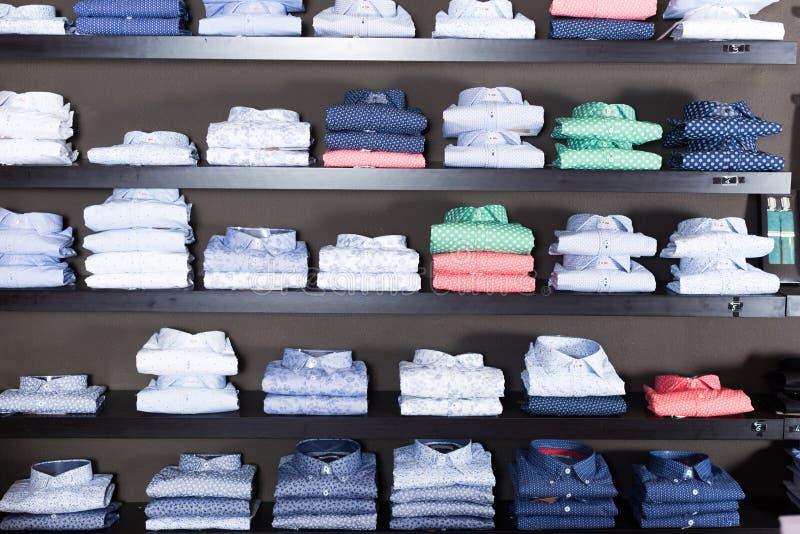 Rad av skjortor på shelfs arkivfoton