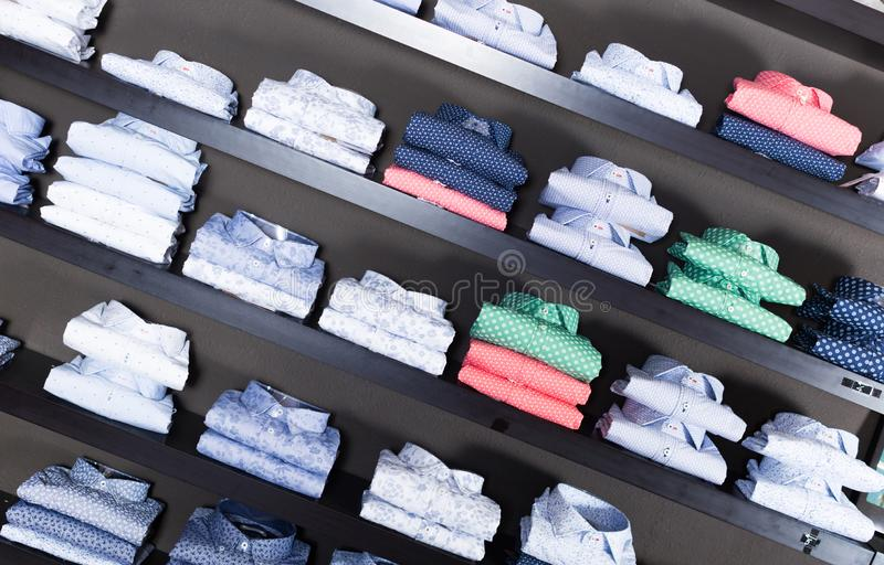 Rad av skjortor på shelfs i manboutique royaltyfri bild
