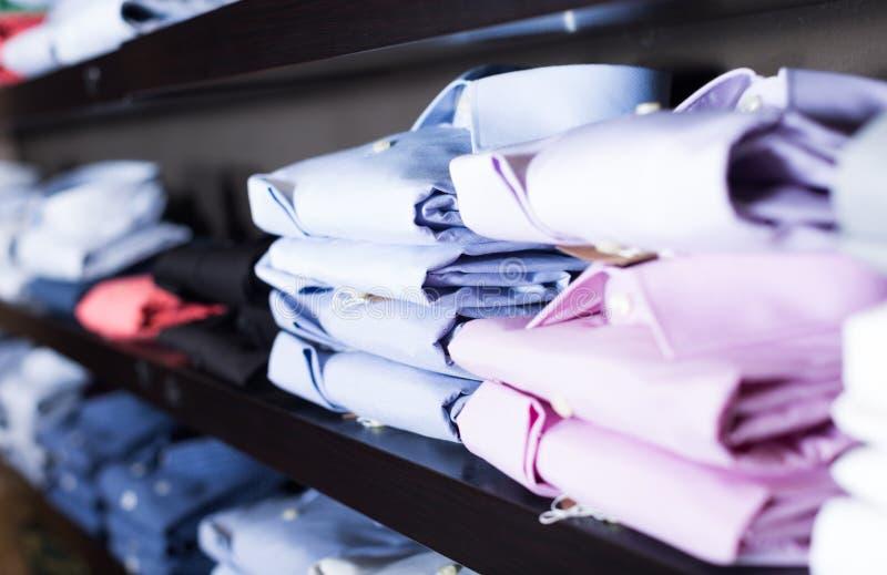 Rad av skjortor på shelfs i manklädlager royaltyfri foto