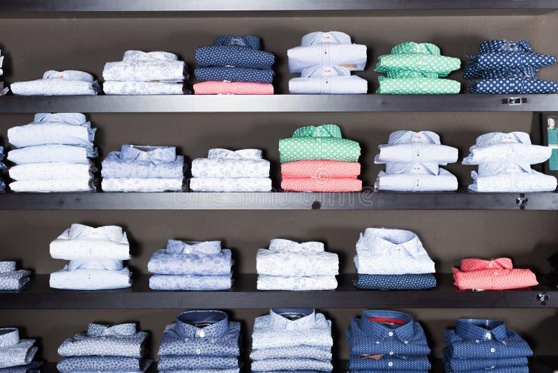 Rad av skjortor på shelfs i manklädlager arkivbild