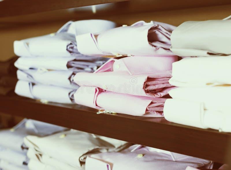 Rad av skjortor på shelfs i visningslokal royaltyfri foto