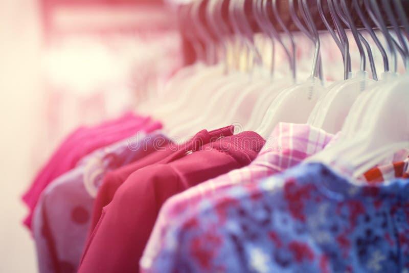 Rad av sommarskjortor som h?nger p? r?knaren, shopping Tyglager, kl?dlager royaltyfria bilder