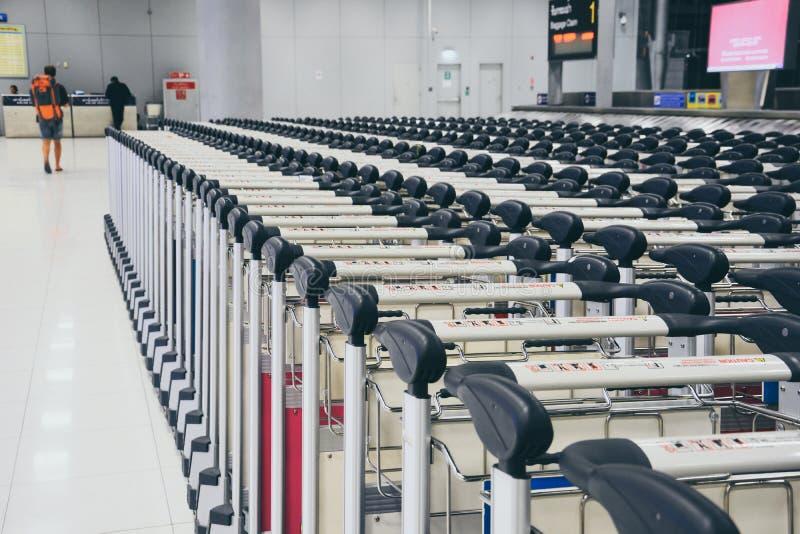 Rad av spårvagnbagage i område för bagagereklamation i ankomstkorridor på den moderna flygplatsen royaltyfria bilder