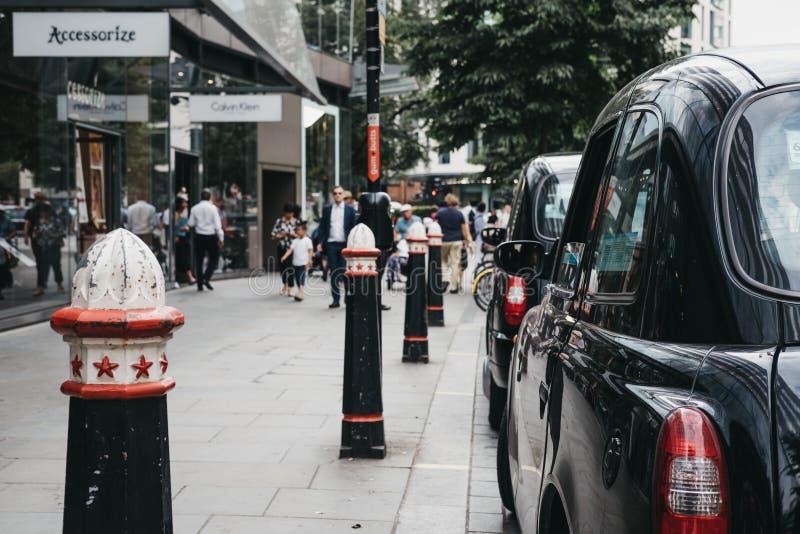 Rad av svarta taxiar som parkeras på en sida av vägen i stad av London, London, UK fotografering för bildbyråer