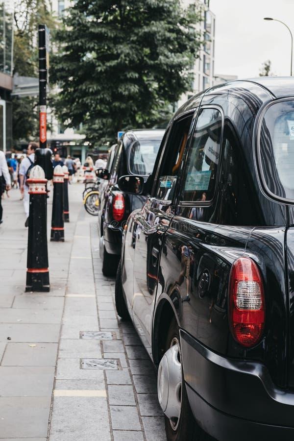 Rad av svarta taxiar som parkeras på en sida av vägen i stad av London, London, UK arkivbilder