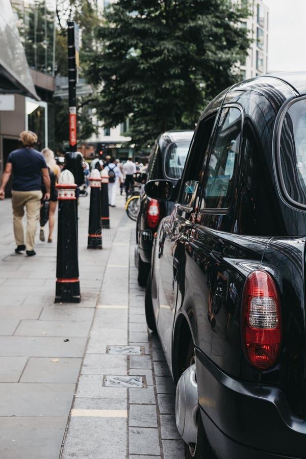 Rad av svarta taxiar som parkeras på en sida av vägen i stad av London, London, UK royaltyfria bilder