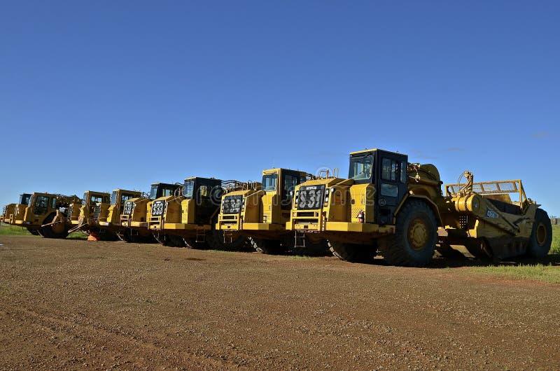 Rad av tunga Caterpillar traktorer arkivbild