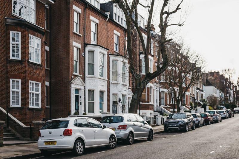 Rad av typiska brittiska terrasserade hus i Hampstead, London, UK, bilar som utanför parkeras royaltyfria bilder