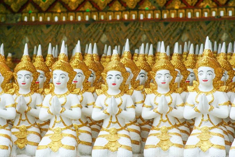 Rad av ursnygga ängelstatygrupper som sitter och att trycka på händerna tillsammans på bröstkorgen i tempel royaltyfria bilder