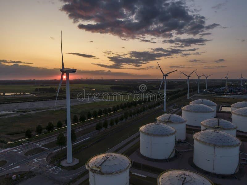 Rad av väderkvarnar som frambringar grön elektricitet på solnedgången i industriellt hamnområde med silor royaltyfri foto